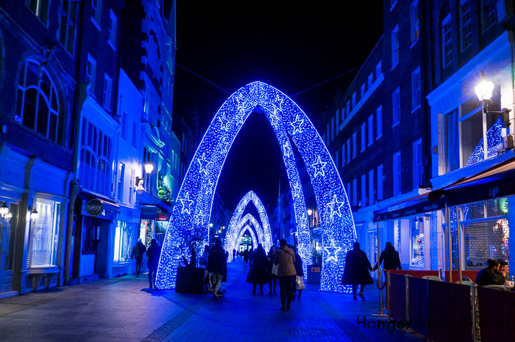 Blue stars under the arches of christmas lights