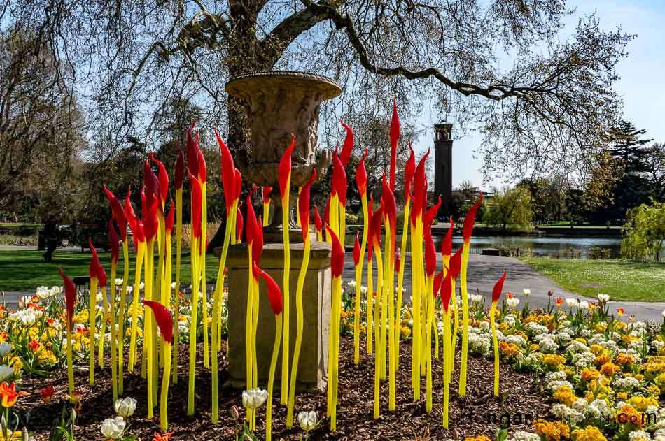 "Chihuly glass stems of red and yellow in front of the Palm House lake Kew ""Paintbrushes"""